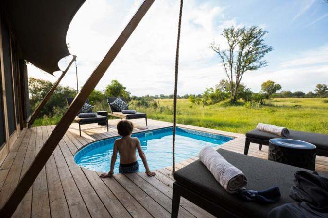 Boy sitting poolside on safari by Staajabu Travel