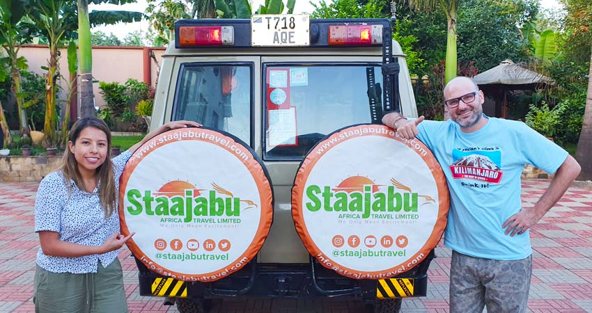 Happy couple posing with Staajabu safari vehicle from the back