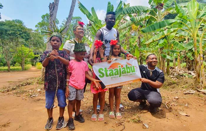 Family posing on safari with Staajabu Travel banner
