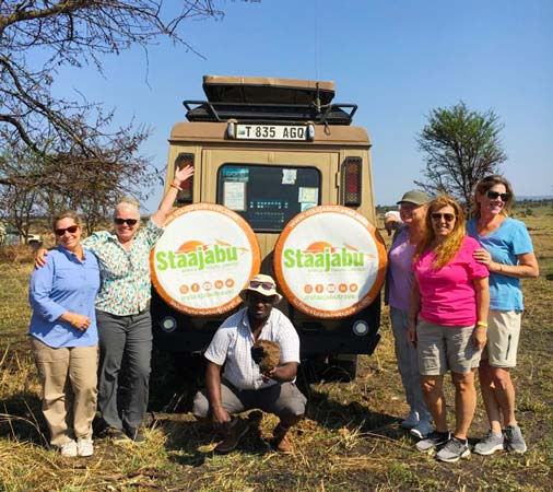 Group of female American tourists posing at the back of a Staajabu Travel safari jeep with a tour guide squatting in the middle