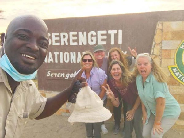 Selfie of tour guide with happy group of tourists at Serengeti entrance gate by Staajabu Travel