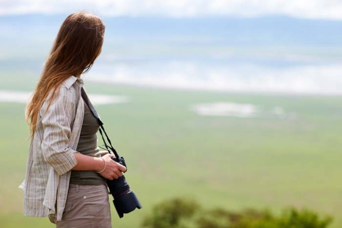Lady with big camera looking inside the Ngorongoro crater from a high vantage point by Staajabu Travel