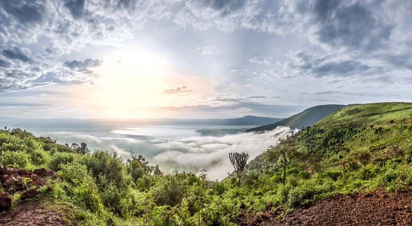 Beautiful view of Ngorongoro crater covered in clouds at dawn by Staajabu Travel