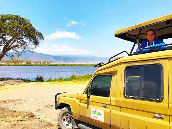 Lady posing inside a Staajabu safari jeep inside the Ngorongoro crater at the Ngoitoktok picnic site