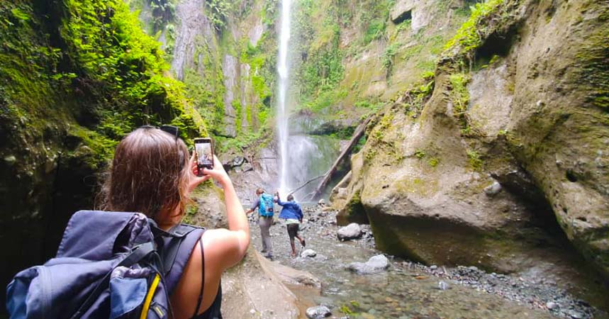 Tourist taking a photo of Themi Hill waterfall during a Staajabu Tour