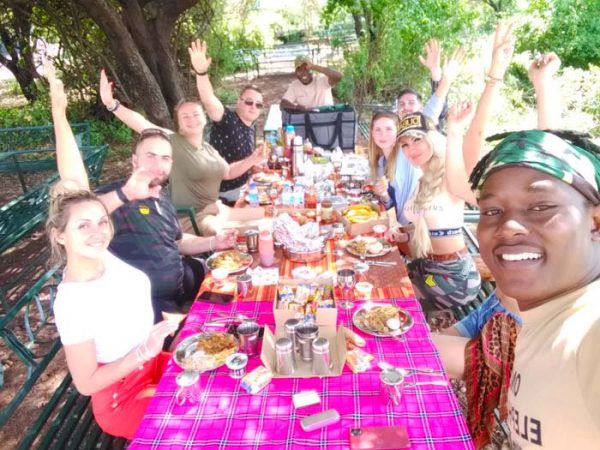 Happy group of tourists having hot lunch in Tarangire on a big table