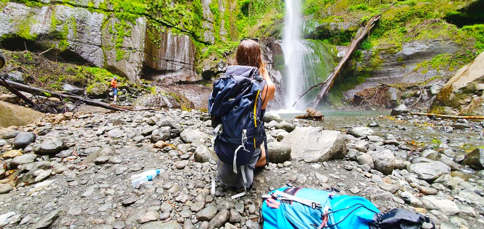 Tourist taking a picture of Themi hill waterfall by Staajabu Travel