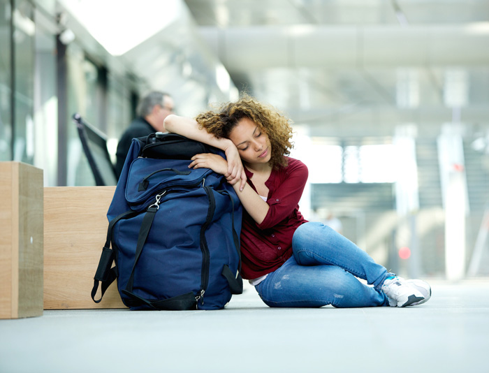 Young woman sleeping on her bag in an airport