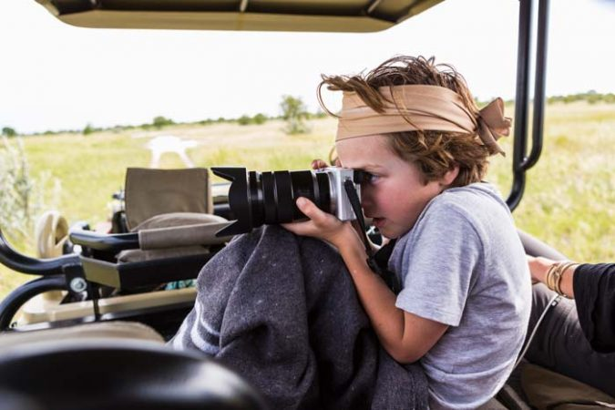 6 year old boy taking pictures from a safari vehicle by Staajabu Travel