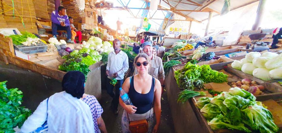 Tourists walking through an isle in the local market in Arusha city