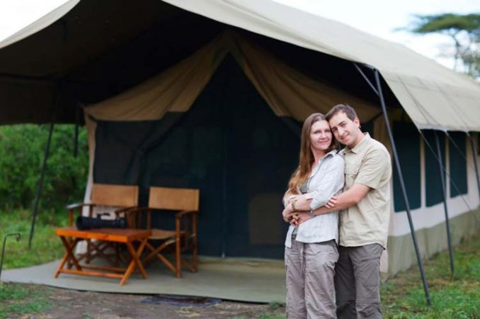 Couple posing infront of a safari tent by Staajabu Travel