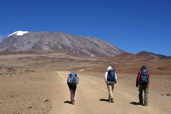3 hikers on the alpine desert of mount Kilimanjaro by Staajabu