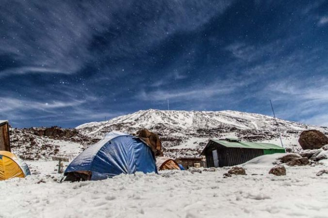 Huts and tents on a snowy day on mount Kilimanjaro by Staajabu Travel