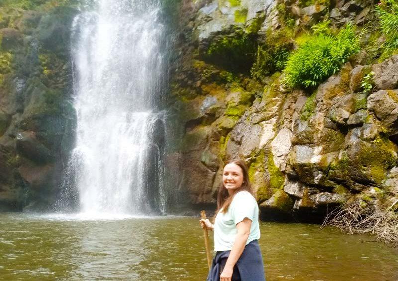 Female tourist standing in front of waterfall in Marangu Kilimanjaro region by Staajabu Travel