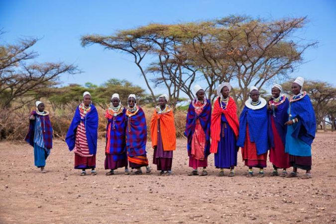 Group of Maasai women standing with Acacia trees on the background by Staajabu Travel