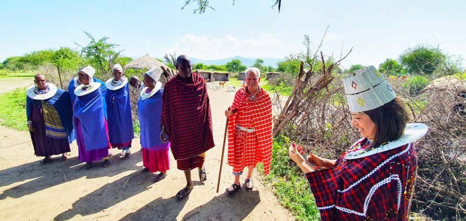 Couple dressed in traditional Maasai clothes standing with Maasai people outside their village by Staajabu Travel