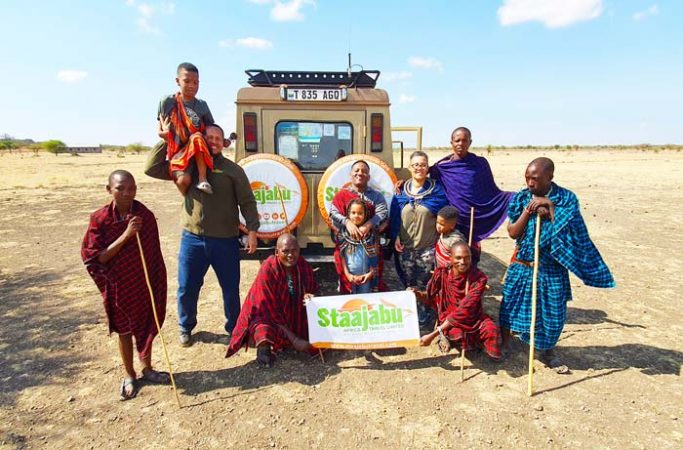 Happy family posing with Maasai warriors behind Staajabu Safari vehicle by Staajabu Travel