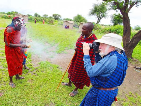 Tourist in traditional Maasai clothing taking pictures in a maasai village