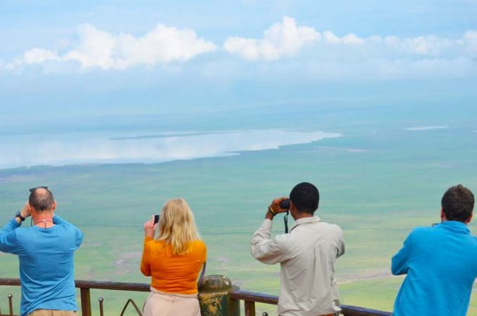 Tourists standing at the Ngorongoro view point with binoculars by Staajabu Travel