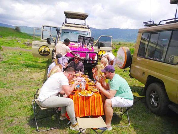 Group of tourists having a picnic lunch inside Ngorongoro crater besides 2 Staajabu Safari vehicles
