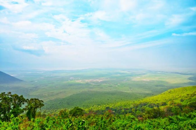 View of the majestic lush green Ngorongoro crater from the top by Staajabu Travel