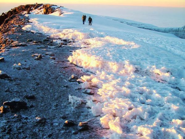 Hikers on the snow covered trail to Uhuru peak at dawn, Africa's highest point by Staajabu Travel