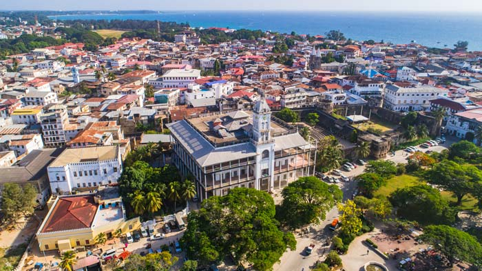 Aerial view of Stone town in Zanzibar with the Indian ocean on the horizon by Staajabu Travel