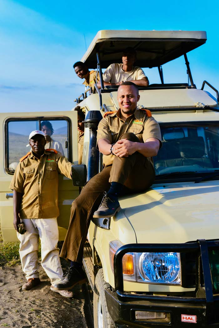 Staajabu Travel team members posing on a safari jeep