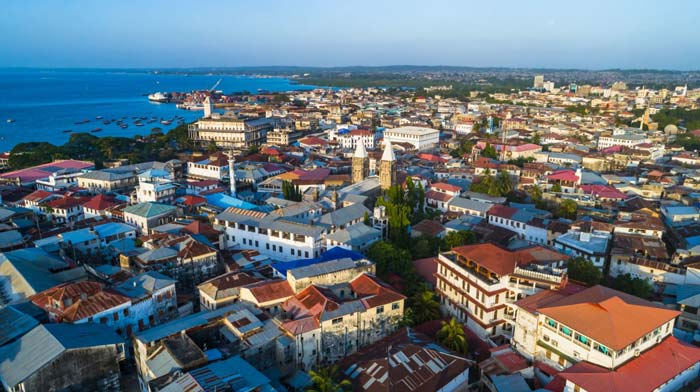 Aerial shot of Zanzibar's stone town with the Indian ocean on the horizon by Staajabu Travel