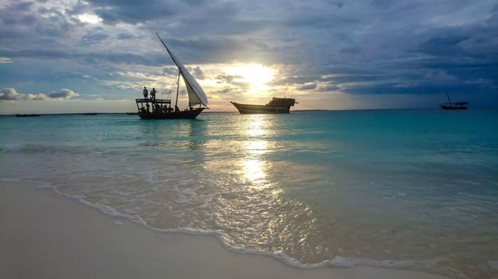 Local fishing boats on the Indian ocean in Zanzibar with a beautiful sunrise during Staajabu travel tour
