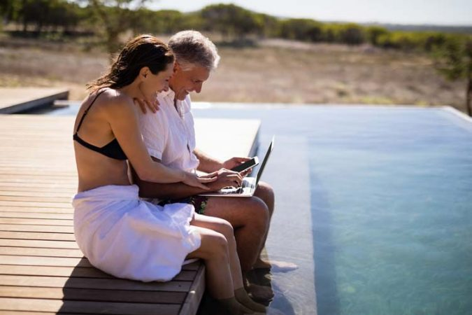 Couple smiling while using a laptop with legs inside an infinite pool overlooking the savanna