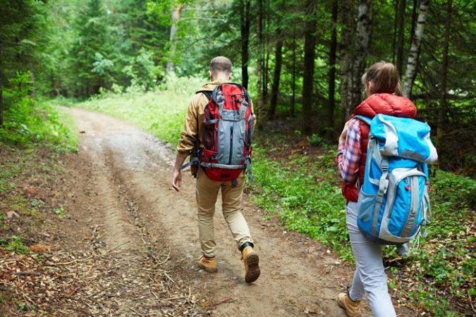 Man and woman walking on a hiking nature trail inside a forest